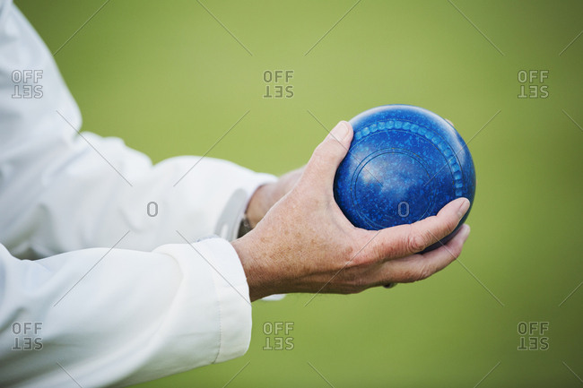 A man holding a blue wooden lawn bowls ball in his hands