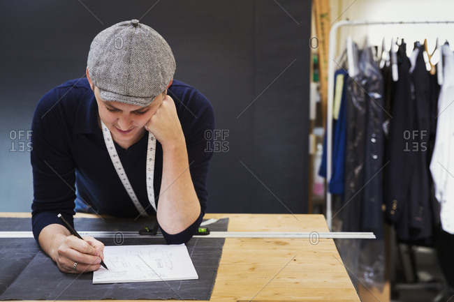 A man at a workbench using pencil and paper, drawing and planning a project