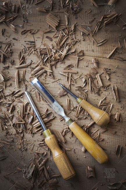 Three hand tools, chisels of different shapes and an awl in shavings on the surface of a piece of planed wood