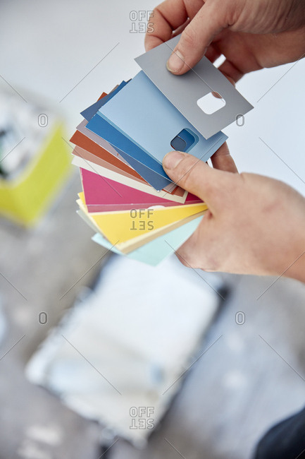 A person holding a paint color chart, choosing a color from the color wheel