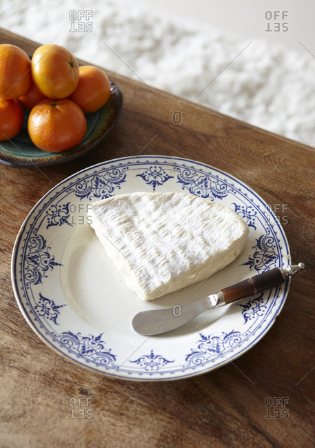 Quarter wheel of Brie cheese on a blue and white china plate with a cheese knife and clementines in the background