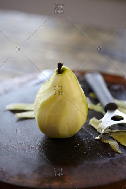 Half peeled pear on a wooden chopping board
