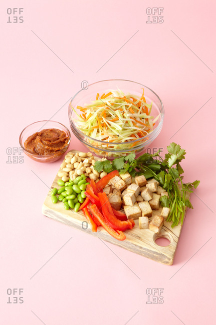 Ingredients for a tofu salad laid out in glass bowls and on a wooden board on a pale pink background