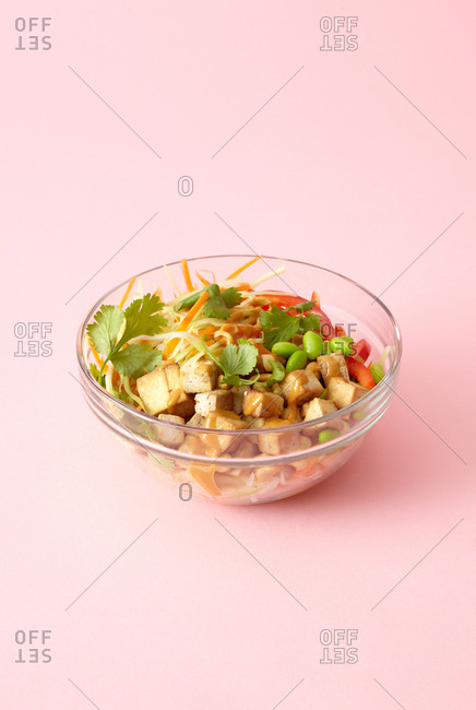 Tofu salad in a glass bowl on a pale pink background