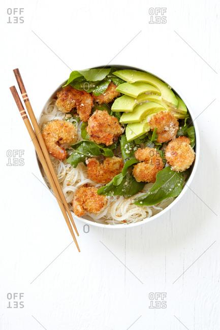 Top view of caesar shrimp and avocado noodle bowl