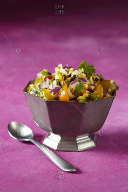 Corn salsa in a silver dish on a fuchsia background