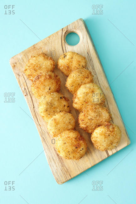 Fried goat cheese rounds on a wooden cutting board against a solid bright blue background