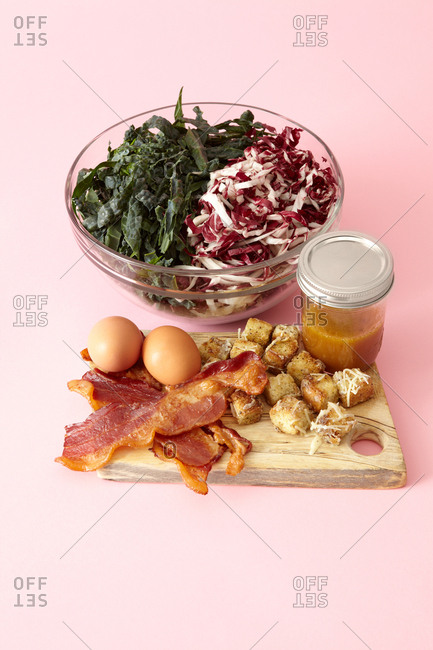 Fresh kale bistro salad ingredients prep with glass bowl, jar, and wooden cutting board against bright pink background