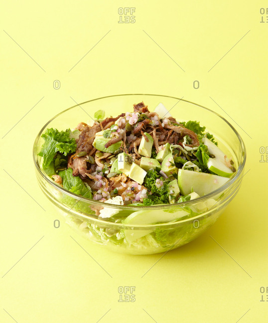 Fresh spicy pork salad in glass bowl against bright yellow background