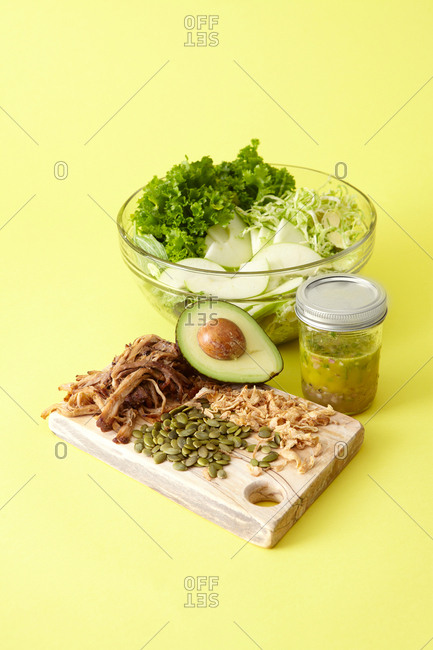 Fresh pork salad ingredients prep with glass bowl, jar, and wooden cutting board against bright yellow background