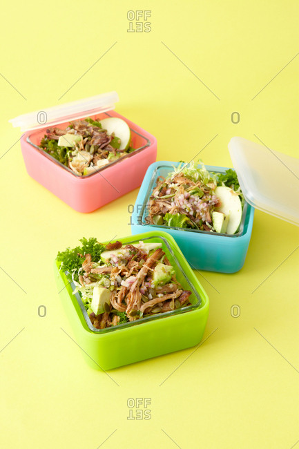 Three salads in colorful square plastic lunch containers against bright yellow background