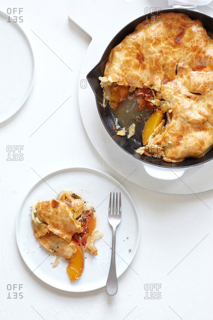 Fresh baked pot pie served from cast iron skillet with plate and fork on white wood background