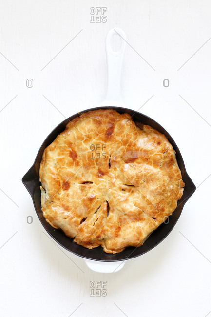 Fresh baked pot pie in cast iron skillet with enamel handle on white wood background