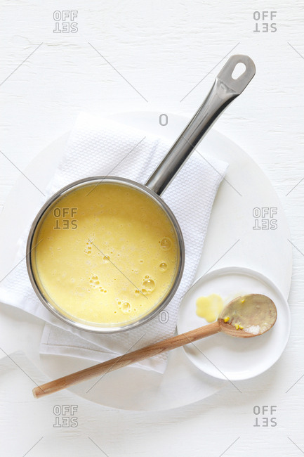 Truffled corn soup in silver pot with wooden spoon on napkin and plate against white background