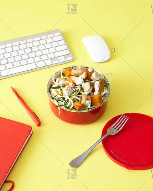Zucchini Buffalo chicken salad lunch in red bowl on yellow computer work desk