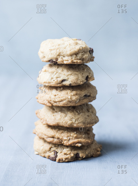 Stack of thick chocolate chip cookies on a blue background