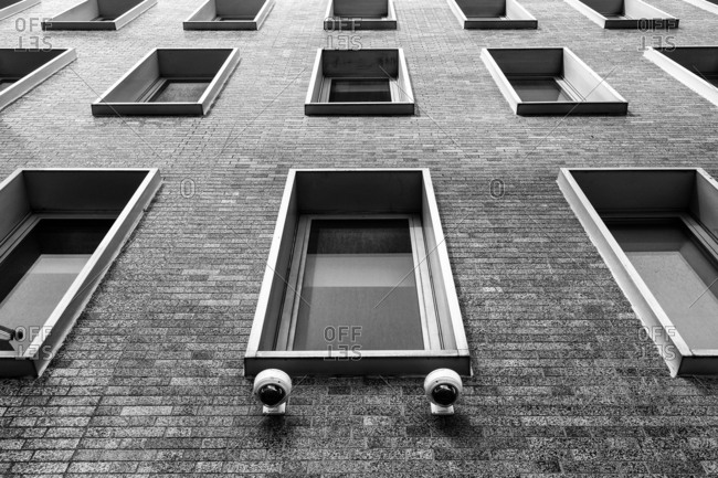Windows and security cameras on exterior of brick building