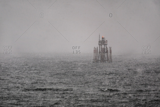 Channel marker shrouded in snow and fog during a storm on Lake Constance