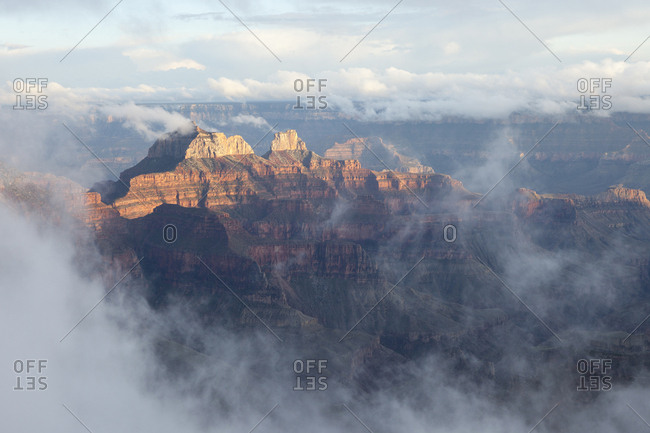 Single peak lit by the sun in a canyon shrouded in mist