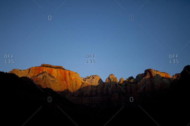 Setting sun illuminates ridge line as seen from canyon floor