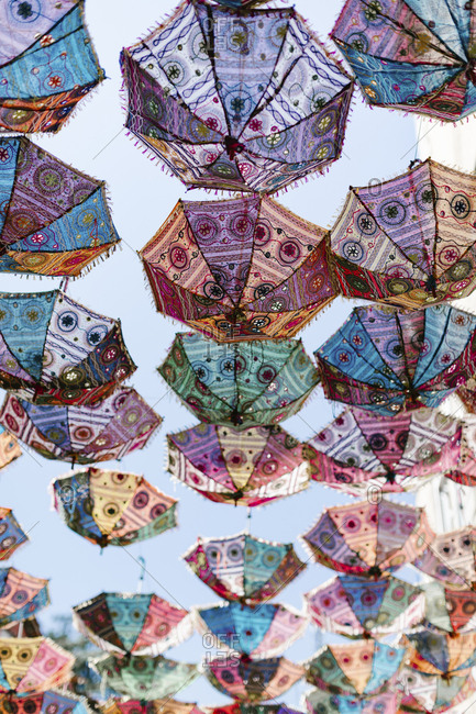 Numerous umbrellas hanging outdoors