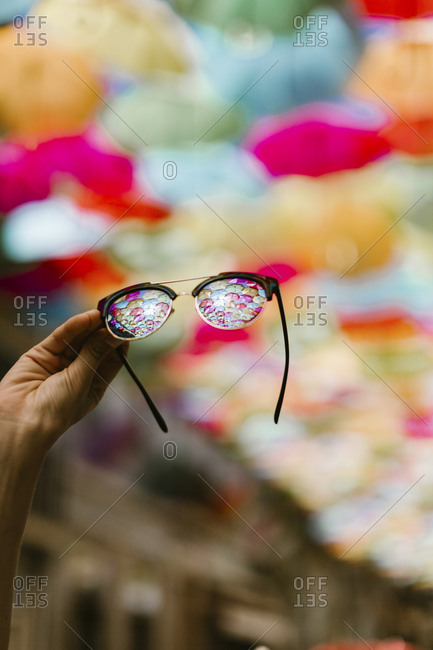 View of colorful umbrellas from a pair of glasses