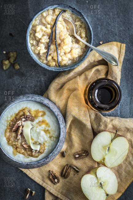 Two bowls of hot porridge served with vanilla beans, butter, apple, and nuts