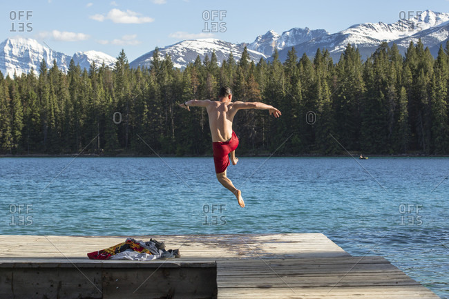 A man in a red bathing suit jumps off a dock into the clear waters of Annette Lake with the snowy Canadian Rocky Mountain in the distance in Jasper National Park, Alberta, Canada.