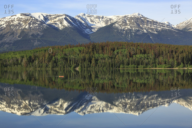 The snow capped Canadian Rocky Mountains and two people paddling a small red canoe create a reflection in Pyramid Lake in Jasper National Park, Alberta Canada.