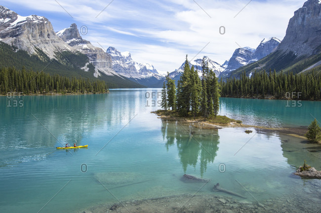 Two tandem kayakers in a yellow kayak, paddle around Spirit Island on scenic Maligne Lake with the snowy Canadian Rockies in the distance in Jasper National Park, Alberta, Canada.