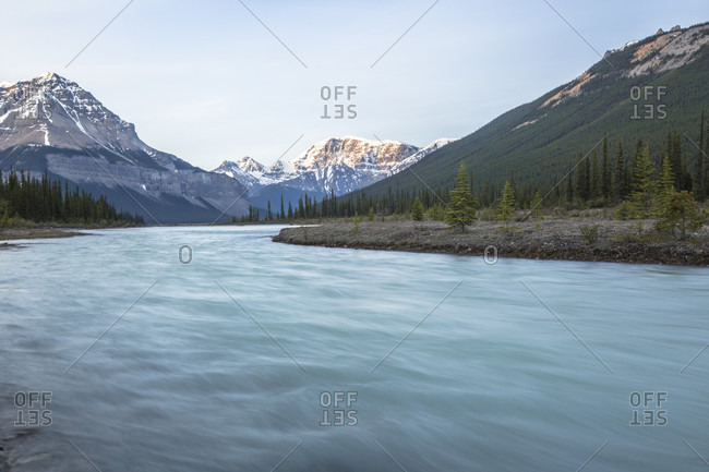 The blue waters of the Bow River cut through the snowy Canadian Rockies at sunrise between Banff National Park and Jasper National Park in Alberta, Canada.