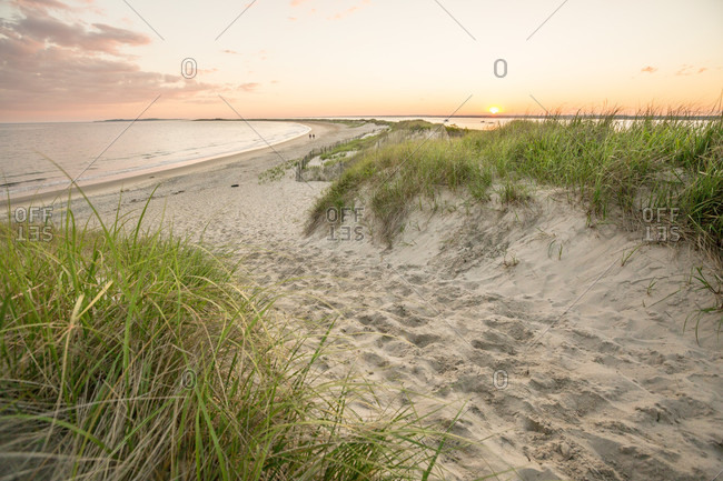 Sun sets over sand dunes and the Atlantic Ocean at Napatree Point in Watch Hill, Westerly, Rhode Island.