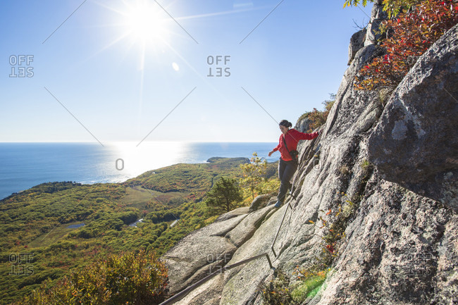 A female hiker in a red jacket carefully climbs high above Bar Harbor on a metal rung ladder while hiking the Precipice Trail on an autumn day in Acadia National Park, Maine.