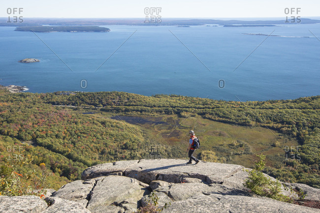 A male hiker in an orange vest hikes to a vantage point at the top of the Precipice Trail in Acadia National Park, while overlooking the ocean and Bar Harbor Maine.