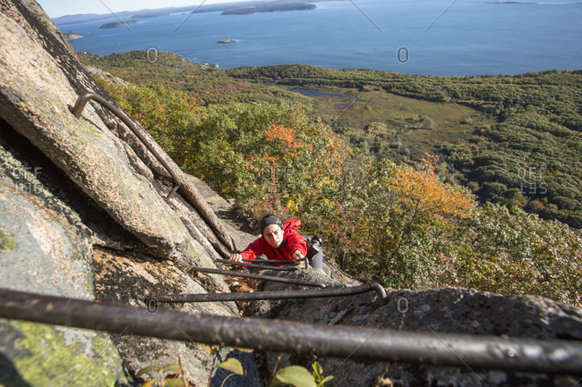 A female hiker in a red jacket climbs high above Bar Harbor on a metal rung ladder while hiking the Precipice Trail on an autumn day in Acadia National Park, Maine.