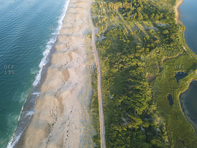 The turquoise Atlantic ocean, orange sands and green trees are seen from an aerial perspective a beach in Weekapaug, Westerly, Rhode Island