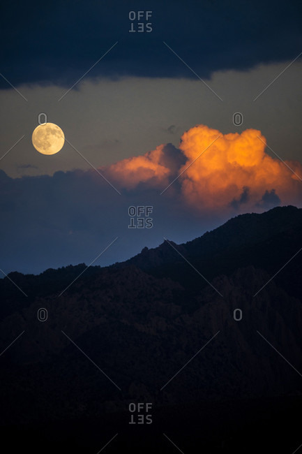 Scenery with full moon at sunset above silhouette of mountains, Eastern Sierra, Buttermilks, California, USA