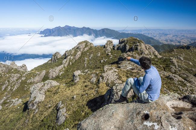 Male hiker sitting on summit of Morro do Couto in Mantiqueira Mountains, Itatiaia National Park, Rio de Janeiro State, Brazil