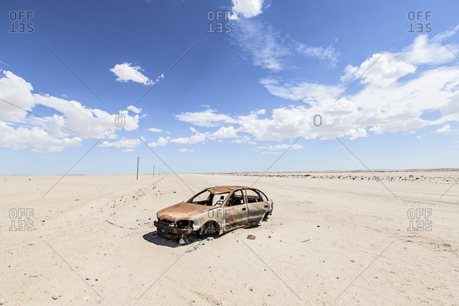 abandoned car wreck sitting in desolate Namib Desert, Swakopmund, Erongo Region, Namibia