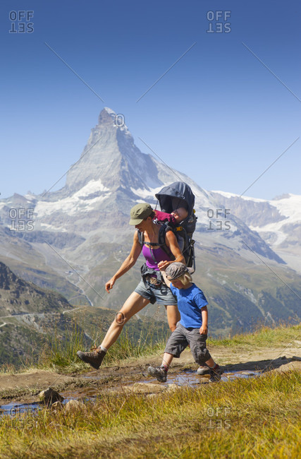 Family of mother with two sons hiking in Swiss Alps with famous Matterhorn in background, Zermatt, Valais, Switzerland