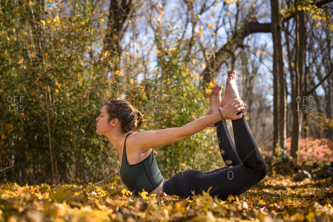 Side view of young woman in heart opening yoga pose amidst fallen autumn leaves, North Kingstown, Rhode Island, USA