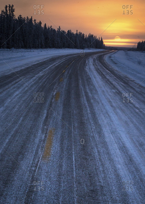 Poor, icy snow-covered road conditions stand in contrast to a beautiful sunset outside Hay River, Northwest Territories in the Canadian north.