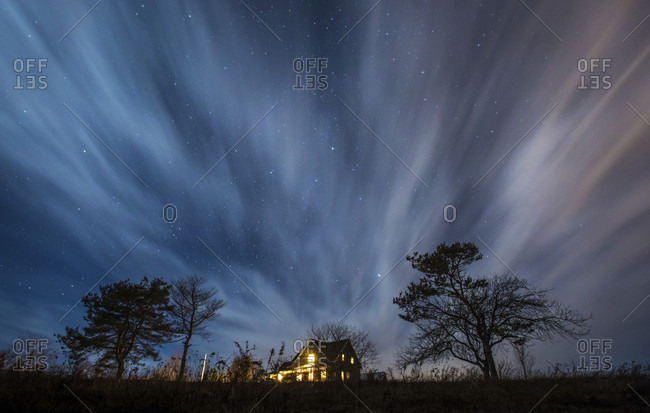 Clouds streak by during a dramatic night time long exposure of a country house surrounding by trees in the rural Prince Edward Island country side.