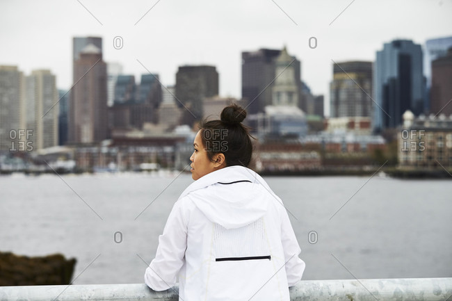 An asian woman poses for a portrait with the Boston city skyline in the background.
