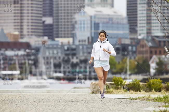 A woman running in East Boston with Boston Harbor and city buildings in the background.