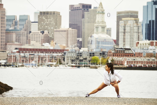 An asian woman stretching before a run in East Boston with the Boston city skyline in the background.