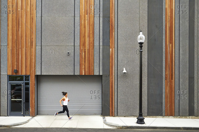 A young asian woman running past a modern city building.