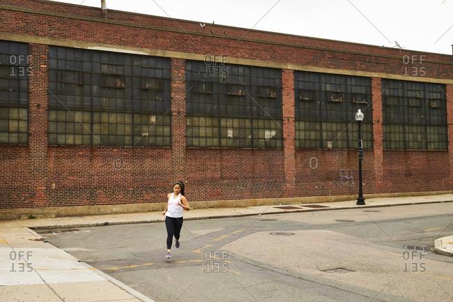 A woman runs around a corner on a city street near an old brick warehouse in East Boston.