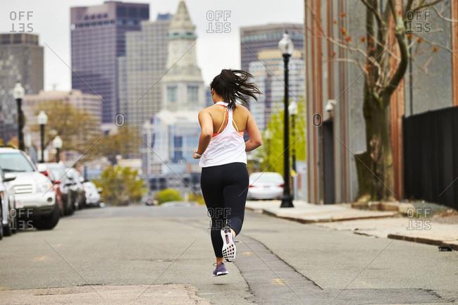 A female runner running towards the Boston skyline.