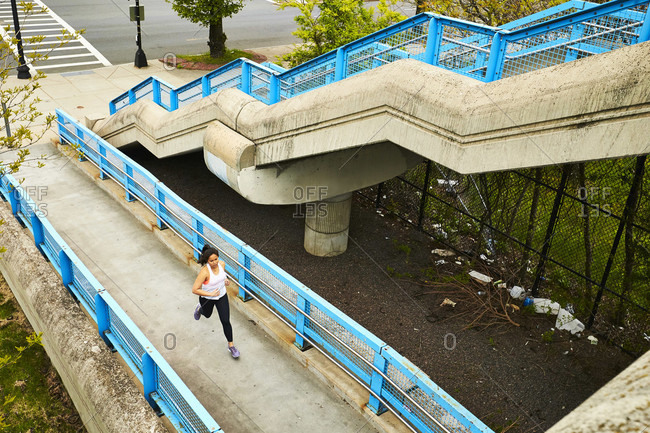 A birds eye view young asian woman running up a ramp near a set of stairs.